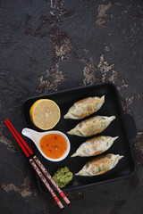 Cast-iron serving tray with pan fried korean dumplings. Flatlay with copyspace on a dark brown stone background, vertical shot