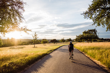Cycling through a field at sunset