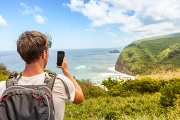 Travel tourist man in Hawaii beach USA vacation taking photo with mobile phone device of ocean landscape mountains background. Pololu Valley beach hike, Big Island, Hawaii.