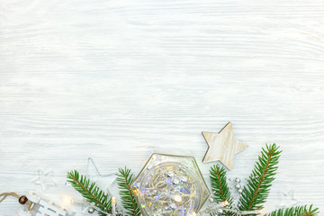 wooden and glass christmas stars with lights garland and fir tree branch on white background