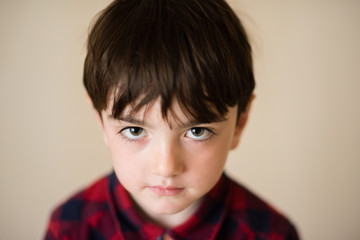 portrait of small lonely sad pensive caucasian boy with big eyes in plaid shirt
