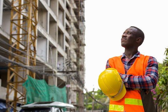 Thoughtful young black African man construction worker holding c