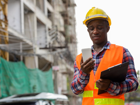 Young black African man construction worker holding clipboard wh