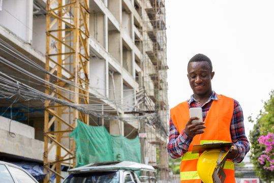 Young happy black African man construction worker smiling and us