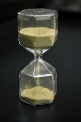Hourglass with flowing sand on table. Time management.