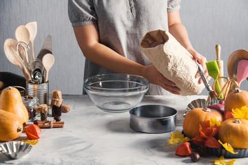Woman cooking baking pack of flour pumpkins autumn time
