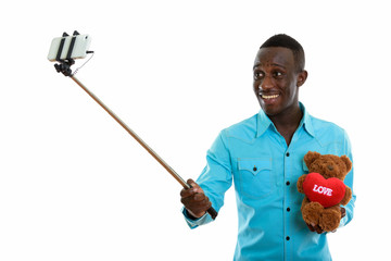 Young happy black African man smiling and holding teddy bear wit