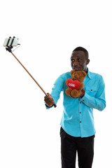 Young black African man holding teddy bear with heart and love s