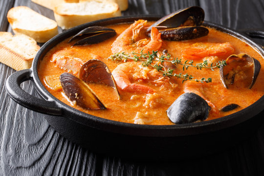 Catalan authentic spicy Suquet de Peix soup with potatoes, shrimps, mussels, herbs and fish with picad close-up. horizontal