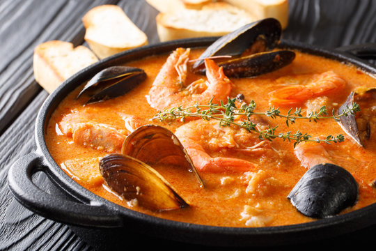 The rich taste of seafood Suquet de Peix soup with potatoes, herbs and fish with the addition of picada close-up in a saucepan. horizontal