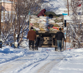 Workers collect garbage in a truck in winter