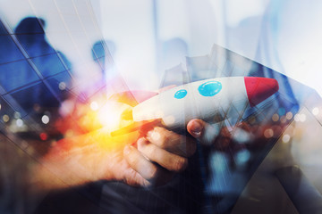 Businessman launches his startup company. Hand holding a wooden rocket. double exposure with light effects