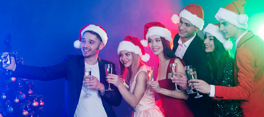 Photo on New Year party. Group of happy friends in santa hats is celebrating the new year or christmas with champagne in hands and have a fun together