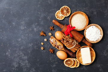 Bakery background with baking ingredients for christmas cooking top view. Flour, brown sugar, eggs and spices top view.