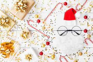 Christmas background of golden confetti, gift or present boxes and funny Santa on white table top view. Flat lay.