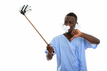 Studio shot of young black African man patient taking selfie pic