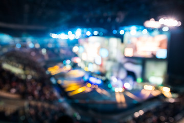 Blurred background of esports event at big arena with a lot of lights and screens.