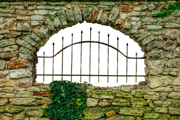 An old stone wall with a metal grille on the opening.