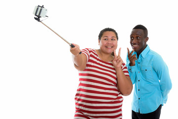 Young mixed race couple using selfie stick to take picture