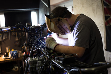 Man made transformation on custom bike. Indoors of custom motorcycle workshop.