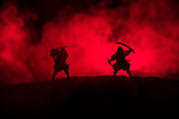 Silhouette of two samurais in duel. Picture with two samurais and sunset sky