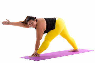 Studio shot of young happy fat Asian woman smiling while bending