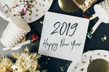 Happy new year 2019 hand brush stroke font in white greeting card on marble table with party cup,party blower,tinsel,confetti.Fun Celebrate holiday party time table top view.