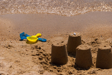 Colorful plastic toy shovel and rake in the sand on the beach by the sea