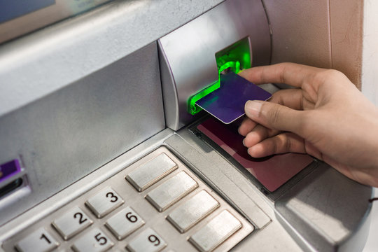 Close up hand of woman using credit card to withdraw money from atm bank machine.