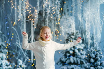 Christmas portrait of happy blonde child girl indoor studio, snowy winter decorated tree on background. New Year Holidays