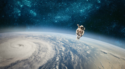 Astronaut in outer space against the backdrop of the planet earth. Typhoon over planet Earth.