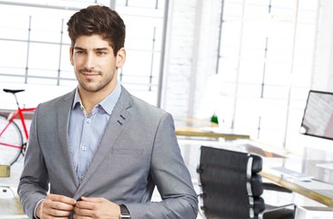 Young man smiling leaving office