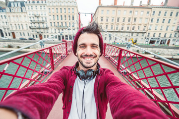 Casual man smile at the camera taking a selfie in the city on travel