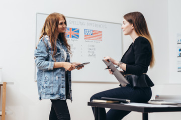 Two female students talking in classroom. College, English language school.