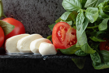 Mozzarella with basil and tomatoes .