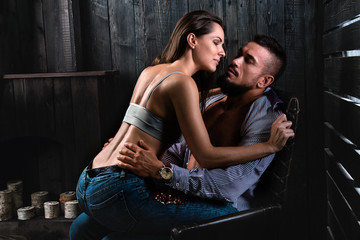 Fitness couple man and woman are kissing on the armchair, loving and smiling