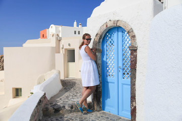 Young woman in white dress in town Oia of Santorini