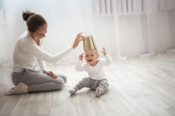 Cheerful baby boy having fun with mother on floor