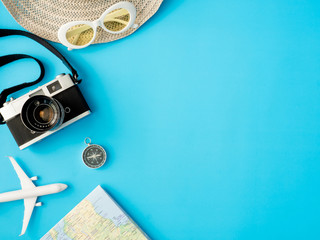 top view travel concept with retro camera films, map, passport, smartphone on blue background with copy space, Tourist essentials, vintage tone effect