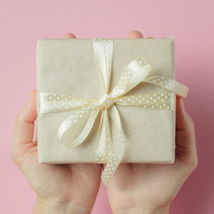 Woman hands holding gift box in palms on pink background, close up top view