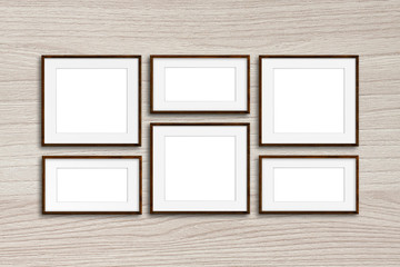 Six brown photo frames mock up on wooden panels wall
