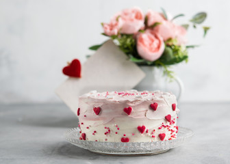 Close Up of a cake decorated with small hearts against a gray background. Romantic love concept. Valentine's, Mother's Day, Birthday Cake card Background.
