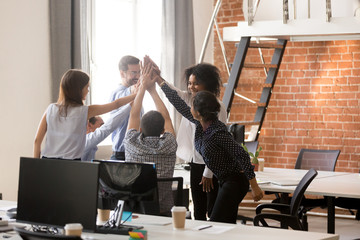 Happy motivated diverse office team giving high five together, excited multi-ethnic employees group celebrating reward, startup success, good teamwork result, engaging in teambuilding concept