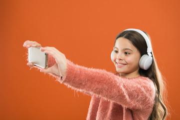Listen for free. Mobile application for teens. Girl child listen music modern headphones and smartphone taking selfie. Get music subscription. Enjoy music concept. Best music apps that deserve listen