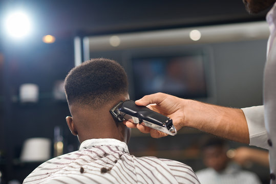 View from back of process of trimming hair in barber shop