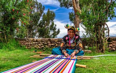 Junge Frau aus Peru beim weben von Alpakawolle für einen Wandteppich