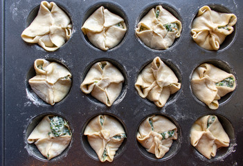 Unbaked spinage and cheese filling in puff pastry dough shells in muffin tin
