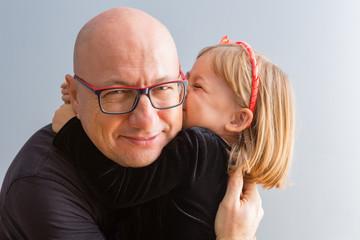 Cute loving little girl kissing her Daddy