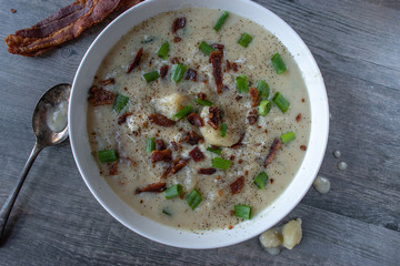 Homemade creamy potato soup with bacon and green onion garnish