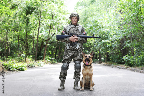 Man in military uniform with German shepherd dog, outdoors